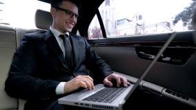 Homem alegre no terno que tem a chamada video, montando no assento traseiro do carro, conversação fotografia de stock royalty free