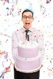 Homem alegre novo que guarda um bolo de aniversário Foto de Stock Royalty Free