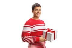 Homem alegre novo que guarda um presente imagens de stock