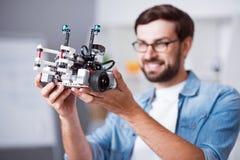 Homem alegre que guarda o robô Imagens de Stock