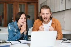Homem alegre que olha felizmente no portátil quando menina que senta-se próximo e que mostra o gesto de mãos dobrado Estudantes q fotografia de stock