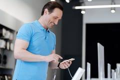 Homem alegre que sorri ao comprar na loja da eletrônica foto de stock royalty free