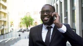 Homem alegre que tem a conversação sobre o telefone celular, conversa com sócios, sucesso imagem de stock