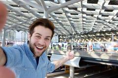 Homem alegre que toma o selfie e apontar fotografia de stock