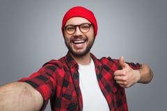 Homem alegre que toma o selfie e que gesticula o polegar-acima Fotografia de Stock Royalty Free