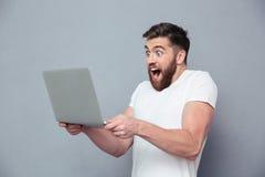 Homem alegre que usa o laptop fotografia de stock
