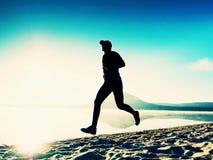 Homem alto do ajuste que corre ao longo da costa de mar na manhã Movimentar-se masculino saudável na praia fotos de stock royalty free
