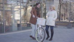 Homem alto que guarda sua bicicleta que fala com a mulher consideravelmente loura no revestimento morno Posição de conversa dos p video estoque