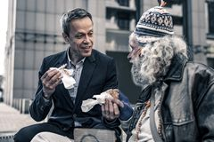 Homem amável comunicativo que fala aos sem abrigo superiores cinzento-de cabelo fotografia de stock royalty free