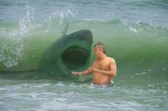 Homem amedrontado do nadador que obt?m a batida pela onda com tubar?o de ataque imagem de stock royalty free