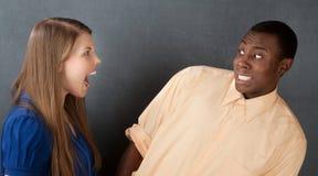 Homem amedrontado pela mulher irritada Fotos de Stock