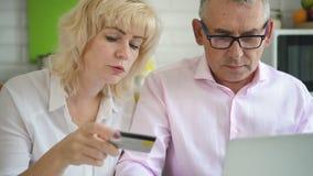 Homem americano e mulher estão procurando por ideias durante o fluxo de trabalho, frente à tela do laptop em iluminação interi video estoque