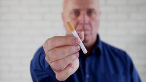Homem amigável no local de trabalho no fumo de relaxamento da pausa e para oferecer um cigarro video estoque