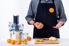 Homem anônimo que veste um avental, preparando o suco de laranja recentemente feito, usando o juicer bonde moderno, conceito saud Fotografia de Stock