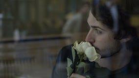 Homem ansioso na amiga de espera do amor com as flores que sentam-se por uma janela em um bar video estoque
