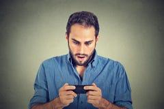 Homem ansioso que olha o telefone que vê fotos das más notícias com emoção assustado na cara imagens de stock royalty free