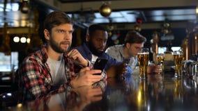 Homem ansioso que verifica as apostas no telefone celular, esportes de observação na barra, app do editor vídeos de arquivo