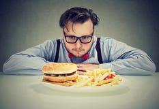 Homem ansioso sobre o fast food insalubre imagem de stock royalty free