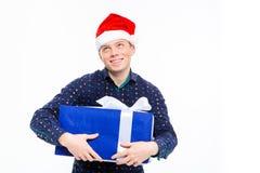 Homem antecipado entusiasmado no chapéu de Papai Noel que guarda o presente Imagem de Stock