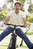 Homem ao ar livre na bicicleta com pés para fora Imagens de Stock