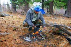 Homem ao lado das fogueiras na madeira Fotografia de Stock