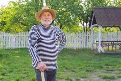 Homem aposentado de irradiação que sorri antes de escavar seu jardim vegetal fotos de stock royalty free
