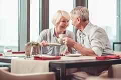 Homem aposentado e mulher que comem o café da manhã junto foto de stock royalty free