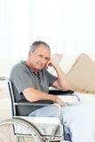Homem aposentado em sua cadeira de rodas imagens de stock royalty free