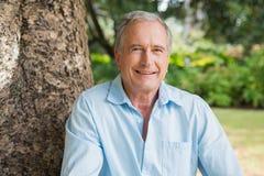 Homem aposentado feliz que senta-se no tronco de árvore fotografia de stock royalty free