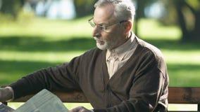 Homem aposentado nos vidros que lê o jornal, sentando-se no banco de parque na manhã vídeos de arquivo