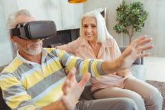 Homem aposentado positivo que veste vidros de VR em casa fotografia de stock