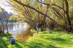 Homem aposentado que aprecia a pesca no país bonito imagem de stock royalty free