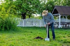 Homem aposentado que aprecia seu tempo ao trabalhar no jardim perto da casa fotografia de stock royalty free