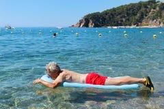 Homem aposentado que joga na água do mar foto de stock