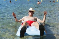 Homem aposentado que joga na água do mar imagem de stock royalty free