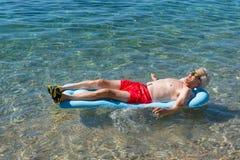 Homem aposentado que joga na água do mar imagens de stock