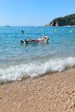Homem aposentado que joga na água do mar fotos de stock royalty free