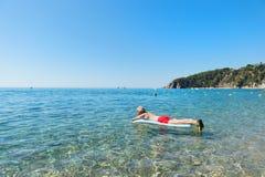 Homem aposentado que joga na água do mar Fotografia de Stock Royalty Free