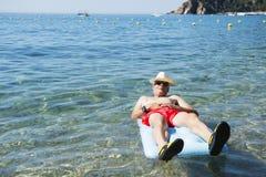 Homem aposentado que joga na água do mar Fotos de Stock