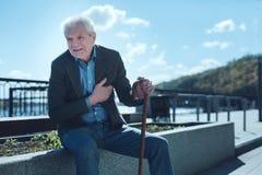 Homem aposentado que sofre da dor do coração foto de stock royalty free