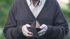 Homem aposentado triste que mostra a carteira vazia antes da câmera, pagamentos miseráveis da pensão vídeos de arquivo