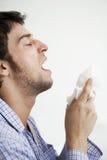 Homem aproximadamente a espirrar no lenço de papel Imagem de Stock Royalty Free