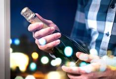 Homem aproximadamente para abrir e estalar a garrafa ou o vinho espumante do champanhe imagens de stock