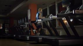 Homem apto dos jovens que dá certo na máquina do piso no gym Homem afro-americano na escada rolante Noite masculina no corredor d vídeos de arquivo