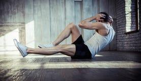 Homem apto dos jovens que exercita em um gym fotografia de stock royalty free