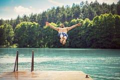 Homem apto dos jovens que faz um salto em um lago fotografia de stock royalty free