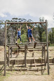 Homem apto e mulher que escalam para baixo a corda durante o curso de obstáculo imagens de stock