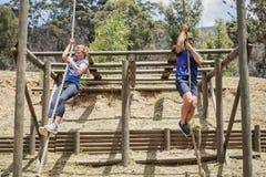 Homem apto e mulher que escalam para baixo a corda durante o curso de obstáculo foto de stock royalty free