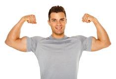Homem apto e muscular que flexiona seu bíceps no branco imagem de stock royalty free