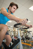 Homem apto focalizado na bicicleta da rotação imagem de stock